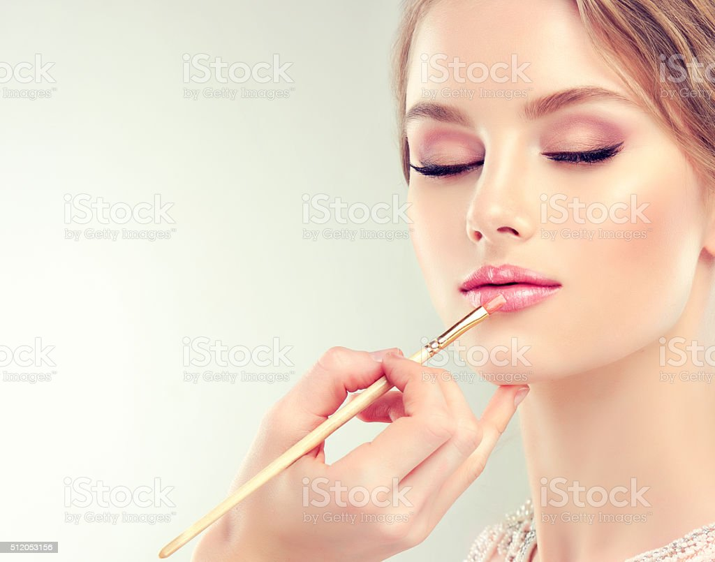Young beautiful woman.Make-up in progress. stock photo