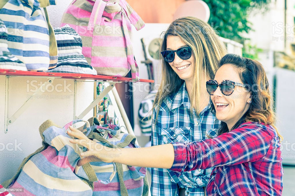 Young beautiful women girlfriends at flea market looking for bag stock photo
