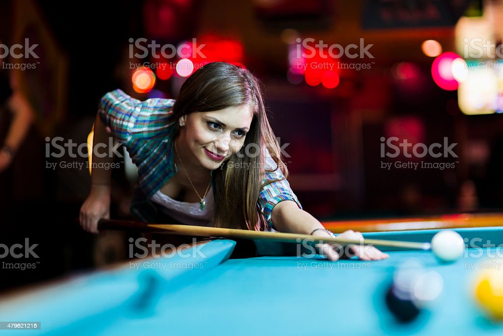 Young beautiful young lady aiming to take the snooker shot stock photo