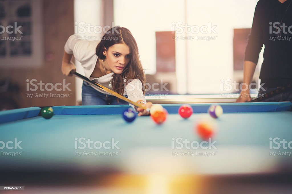Young beautiful young woman aiming to take the snooker shot stock photo