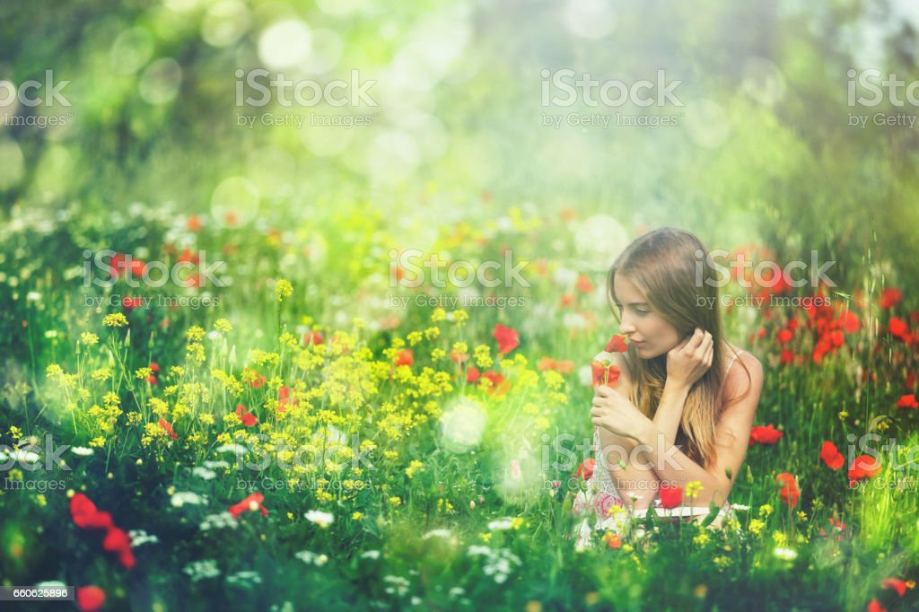 Young beauty between spring flowers in Tuscany, Italy stock photo