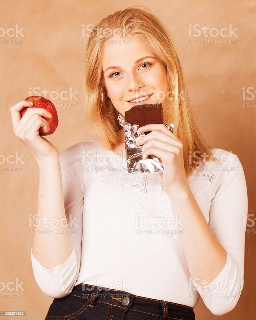 young beauty blond teenage girl eating chocolate smiling, choice between stock photo