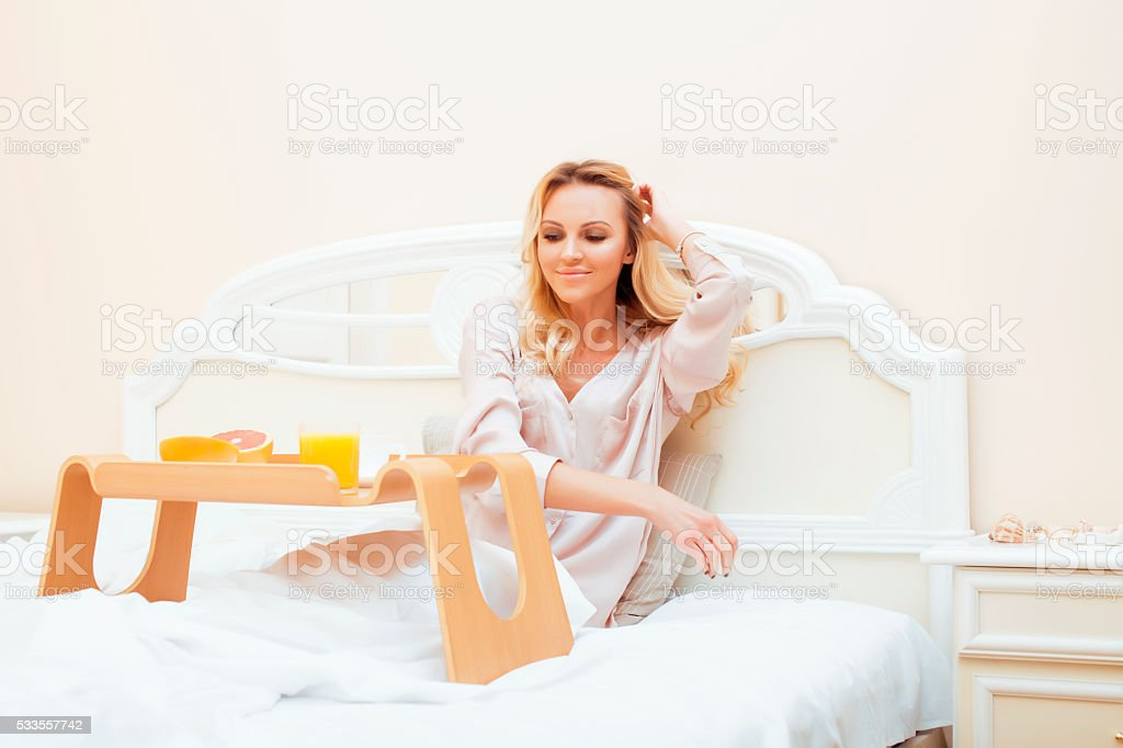 young beauty blond woman having breakfast in bed early sunny stock photo