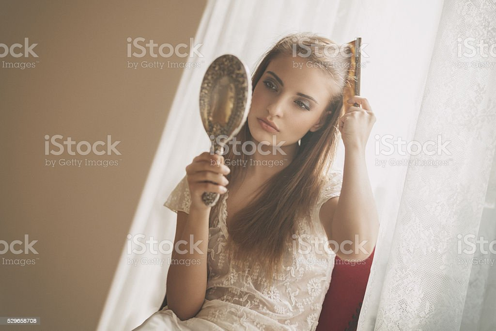 young beauty combing her hair stock photo