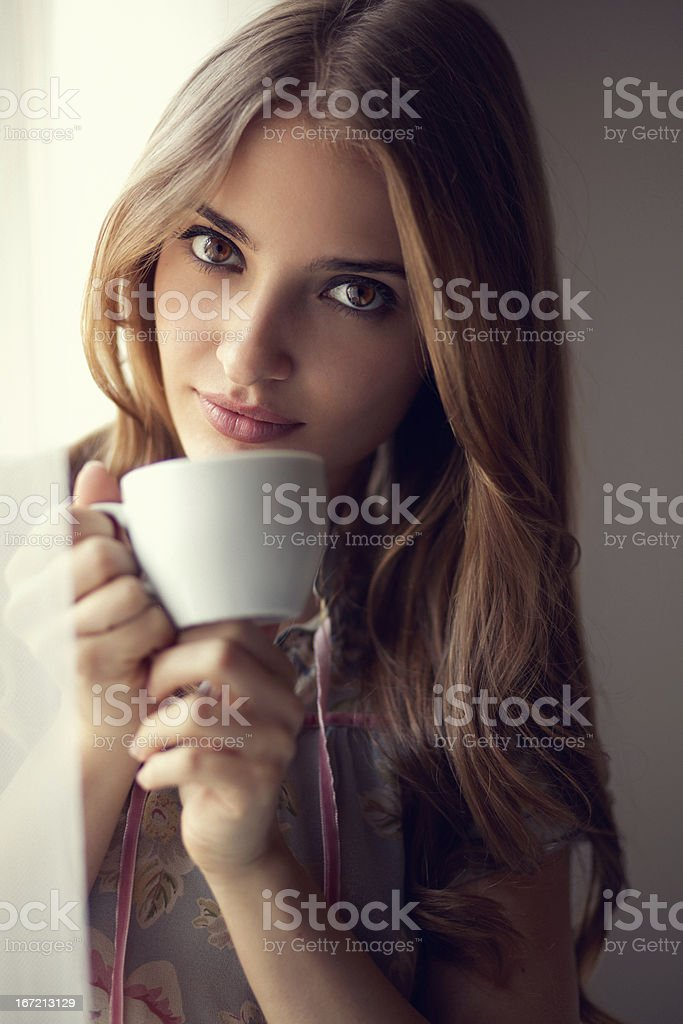 young beauty drinking coffee by the window royalty-free stock photo