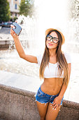 Young beauty girl taking selfie from phone near fountain