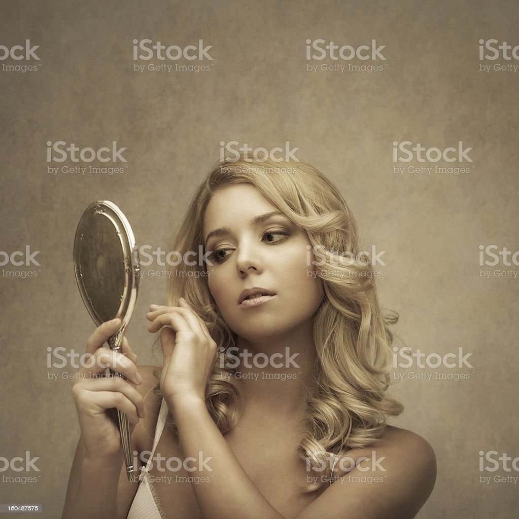 young beauty lookin at herself in a silver hand mirror royalty-free stock photo