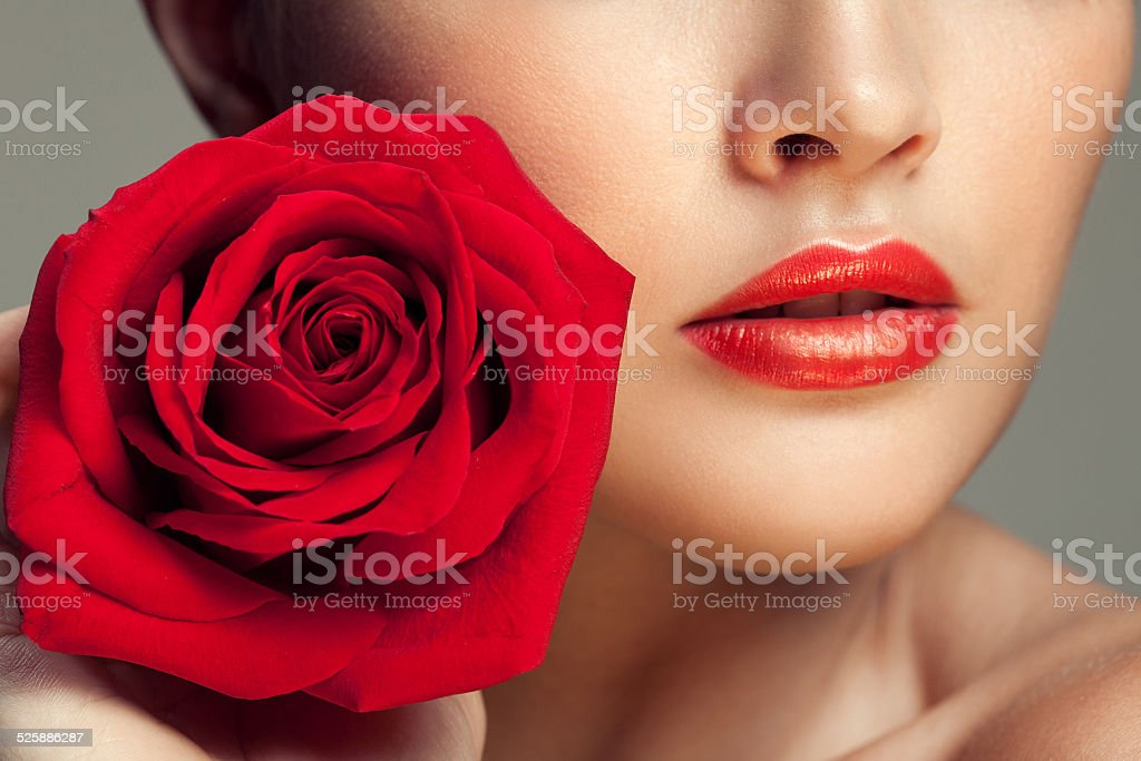 Young beauty model with red rose near lips stock photo