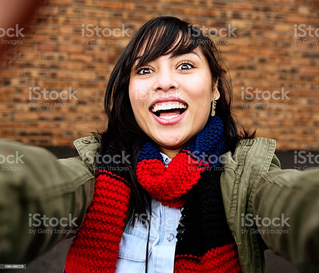 Young beauty smiles as she takes a winter's day selfie stock photo
