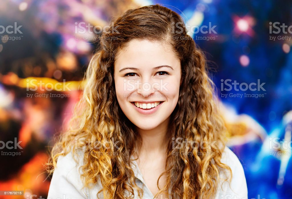 Young beauty smiling in front of astronomical poster stock photo