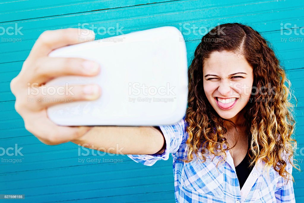 Young beauty taking silly, grimacing selfie stock photo