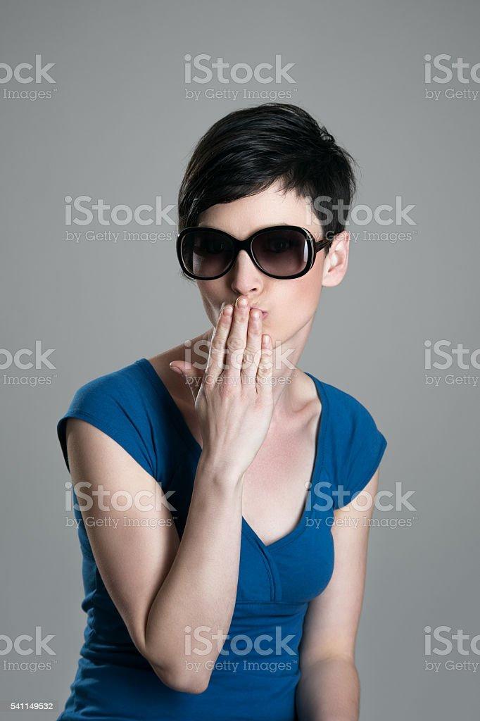 Young beauty wearing sunglasses sending kiss at camera stock photo
