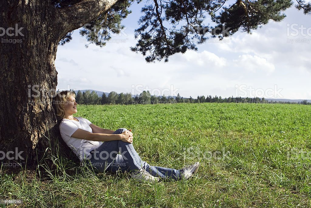 young beauty woman sit under alone tree in field stock photo