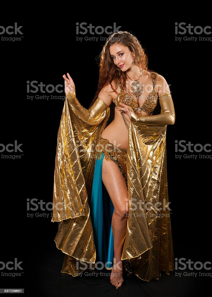 Young belly dancer posing in gold costume with Isis wings stock photo
