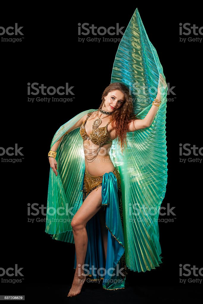 Young belly dancer posing with Isis wings stock photo