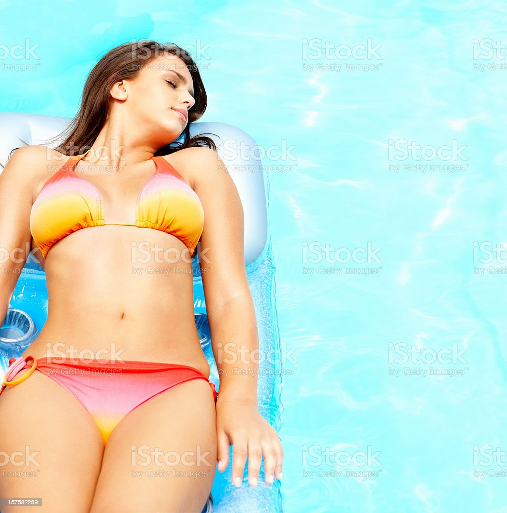 Young bikini woman lying relaxed on a float royalty-free stock photo