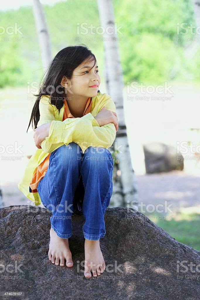 Young biracial girl sitting on rock under trees stock photo