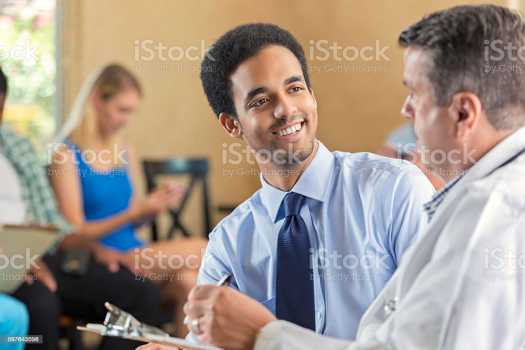 Young biracial man being examined in hospital triage center stock photo
