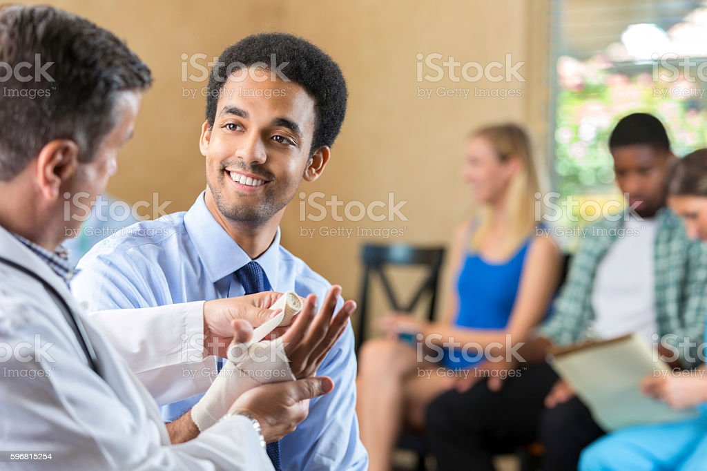 Young biracial patient being examined by hospital doctor stock photo
