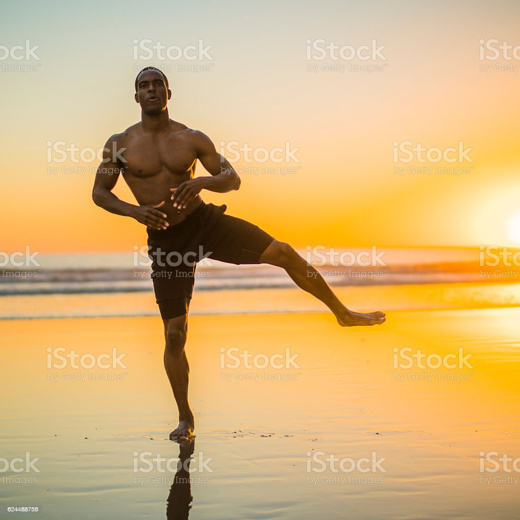 Young black athlete practicing on the beach at sunset stock photo