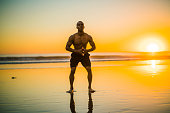 Young black athlete practicing on the beach at sunset