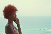 Young black beautiful girl with curly hair speaking on phone