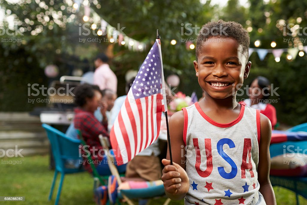 Young black boy holding flag at 4th July family garden stock photo