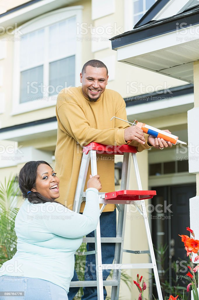 Young black couple doing home repairs stock photo