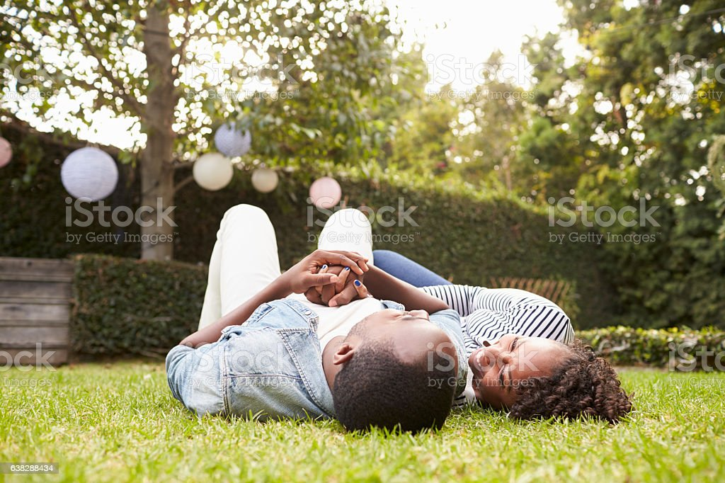 Young black couple lying on grass looking at each other stock photo