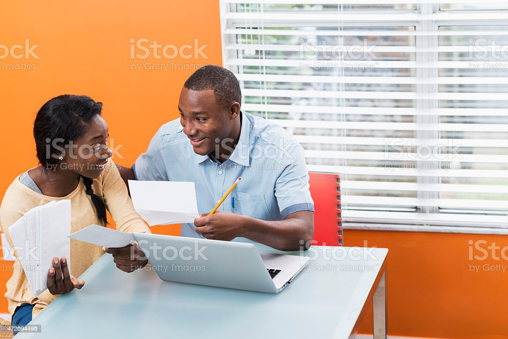 Young black couple paying bills at home stock photo