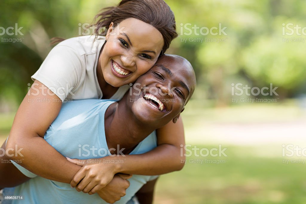 young black couple piggybacking outdoors stock photo