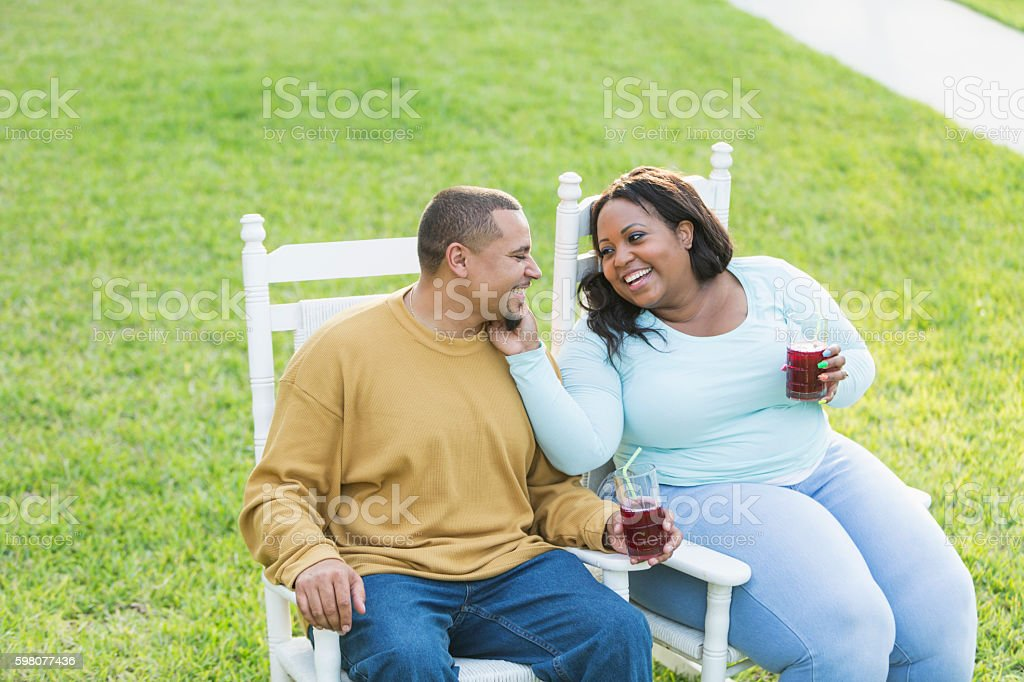 Young black couple sitting, talking, drinking stock photo