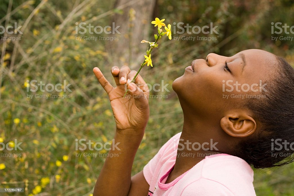 Young black girl blowing on yellow feather royalty-free stock photo