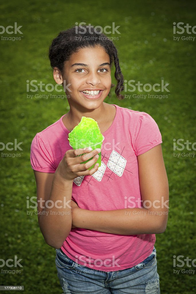 Young black girl with snowcone in summertime. stock photo
