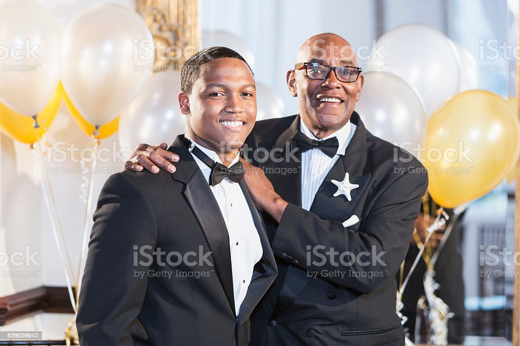 Young black Hispanic man with father in tuxedos stock photo