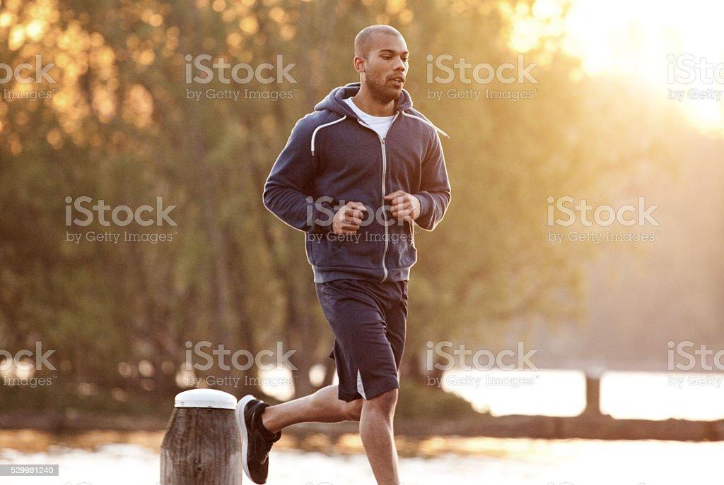 Young black man exercising at dawn at a lake stock photo