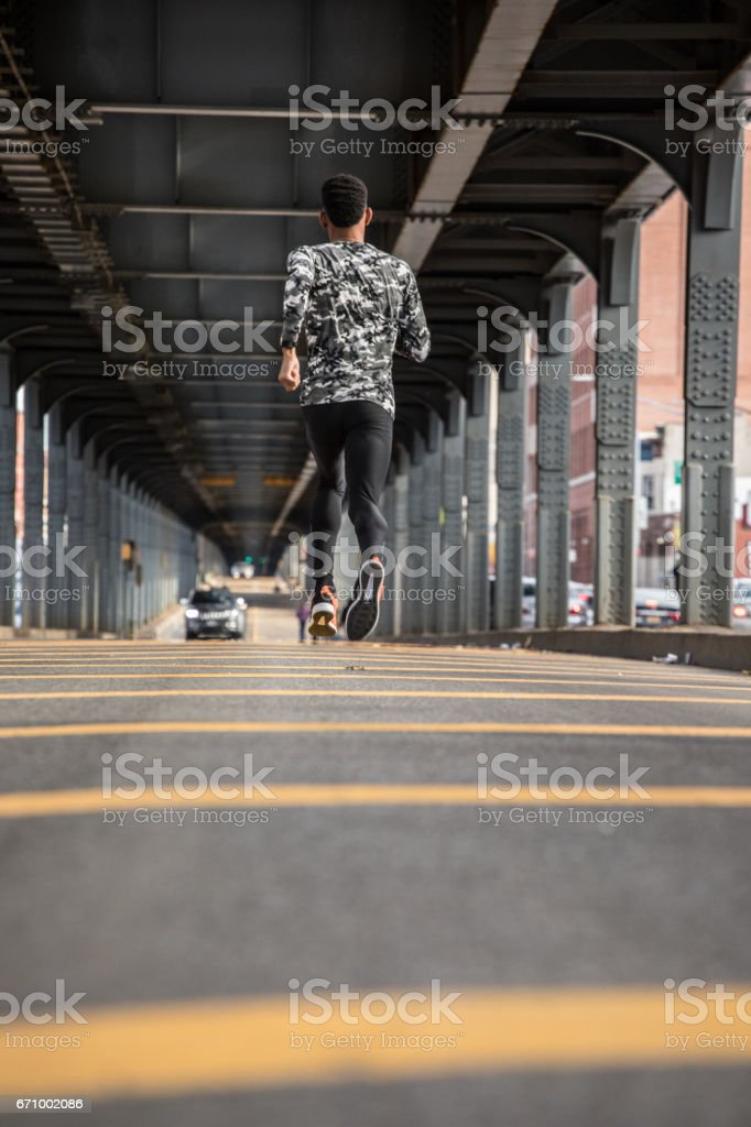 A young, black man goes for a jog in the streets of Brooklyn, NYC stock photo
