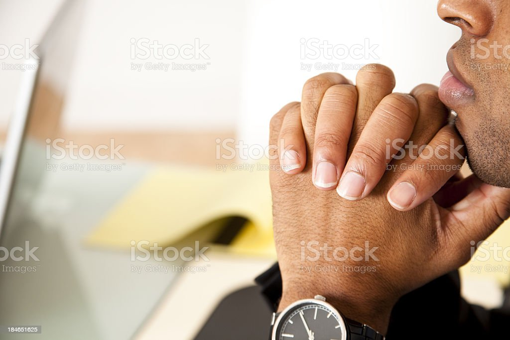 Young black man pondering and listening with clasped hands. royalty-free stock photo