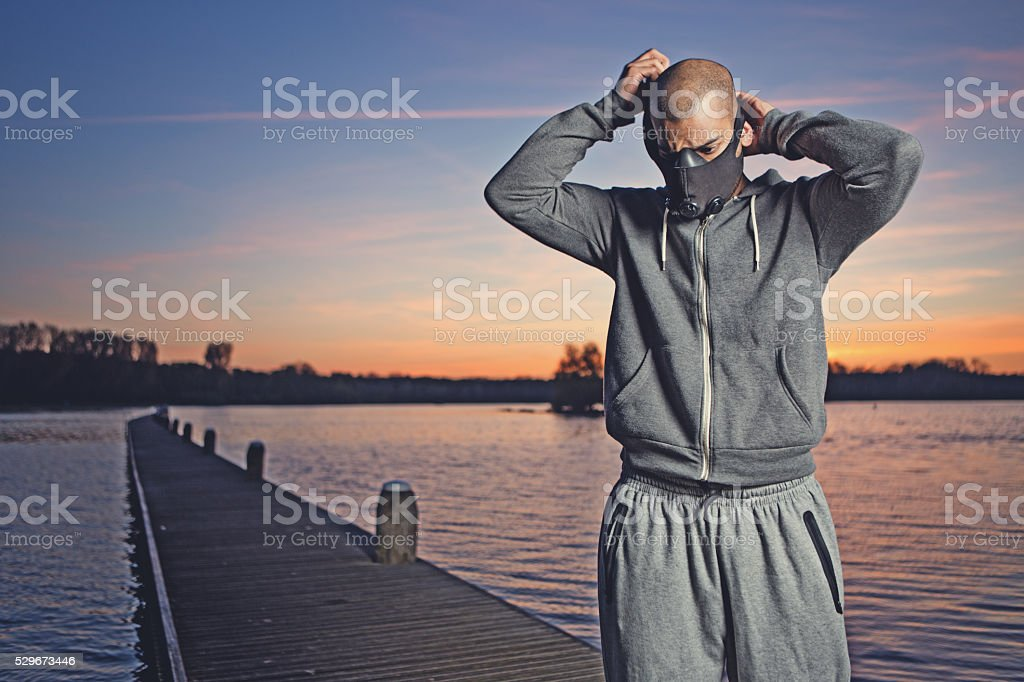 Young black man preparing for exercise at dawn at lake stock photo