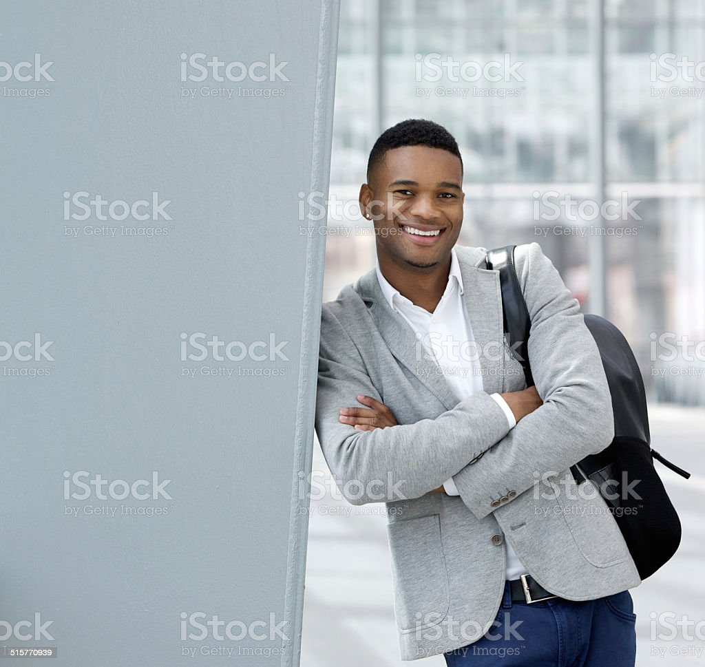Young black man smiling with bag stock photo