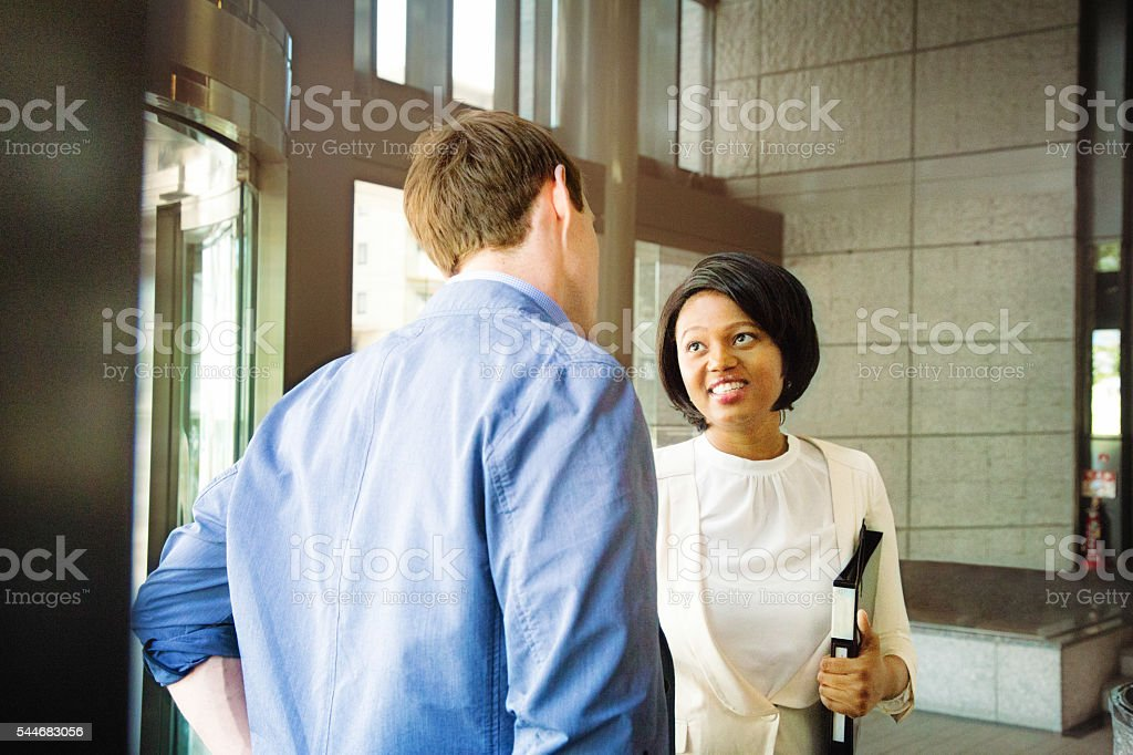Young black professional woman smiles at her colleague stock photo