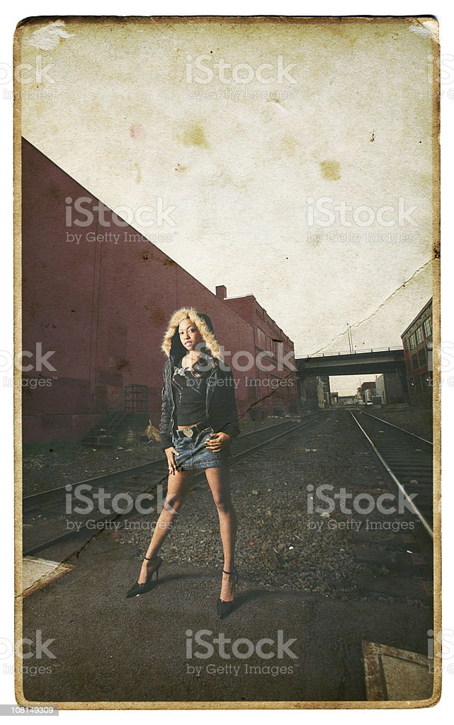 Young Black Woman Between Buildings In Aged Photo. stock photo