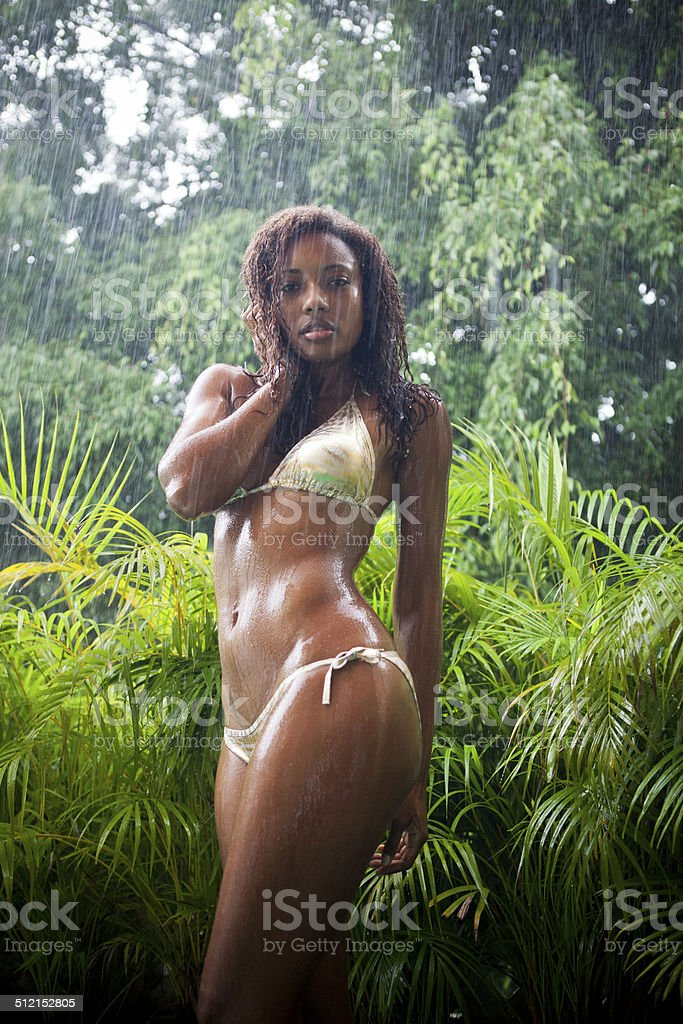 Young black woman dancing under the rain stock photo