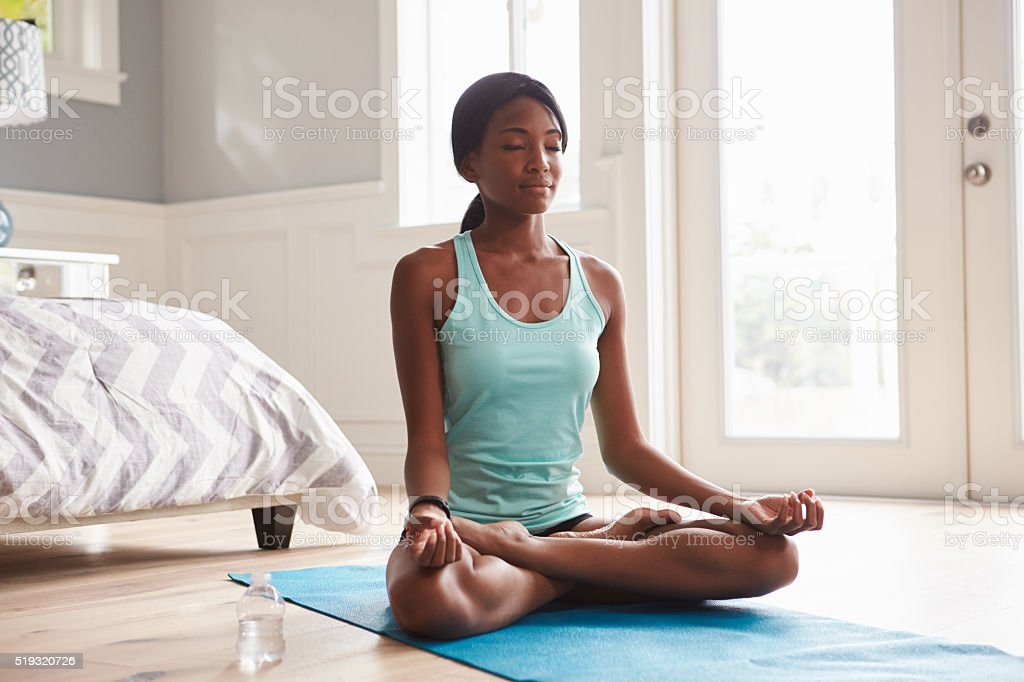Young black woman doing yoga at home in the lotus stock photo