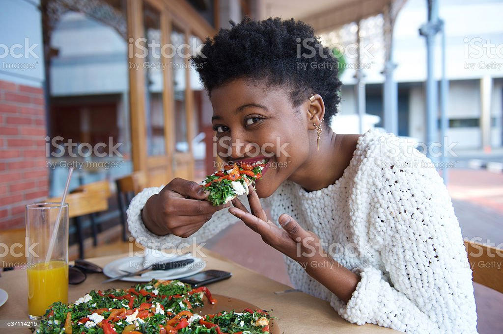 Young black woman eating vegetarian pizza stock photo
