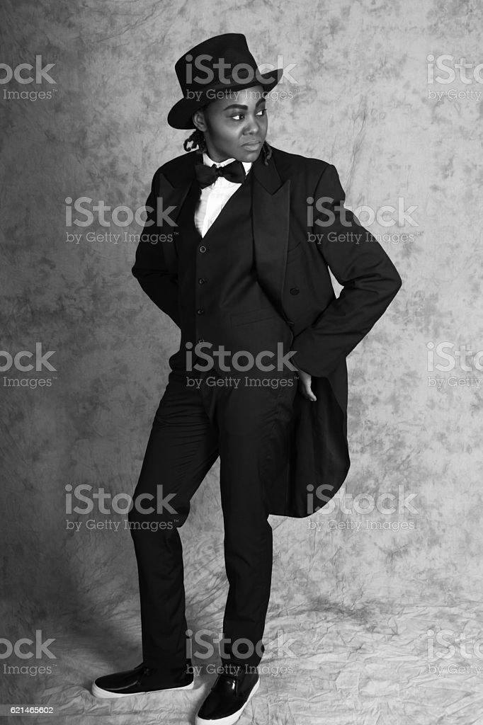 Young black woman in male drag, B&W full length, studio. stock photo
