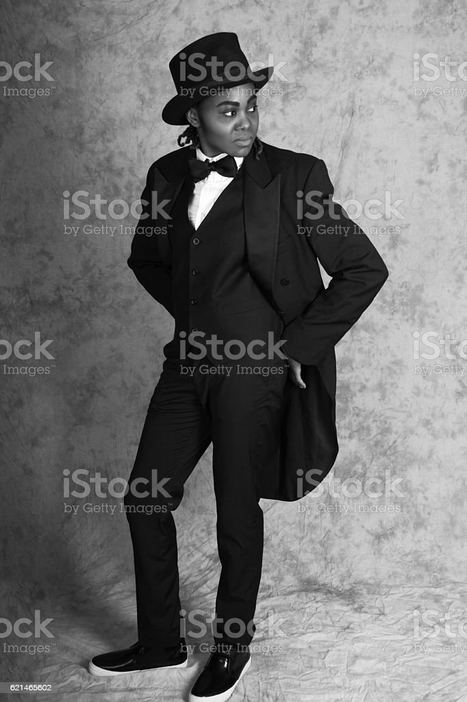 Young black woman in male drag, B&W full length, studio. stock photo