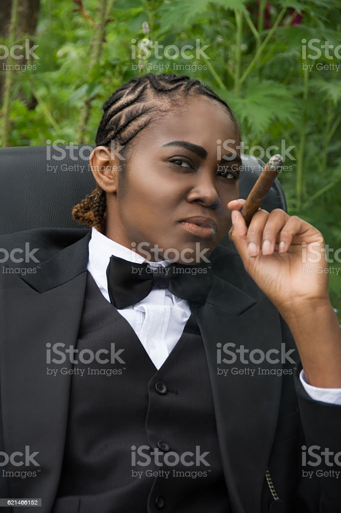 Young black woman in male drag, examining viewer critically. stock photo