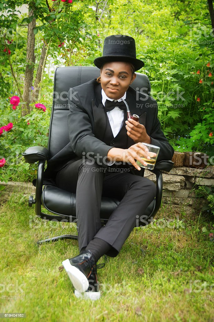 Young black woman in male drag, sitting in summer garden. stock photo