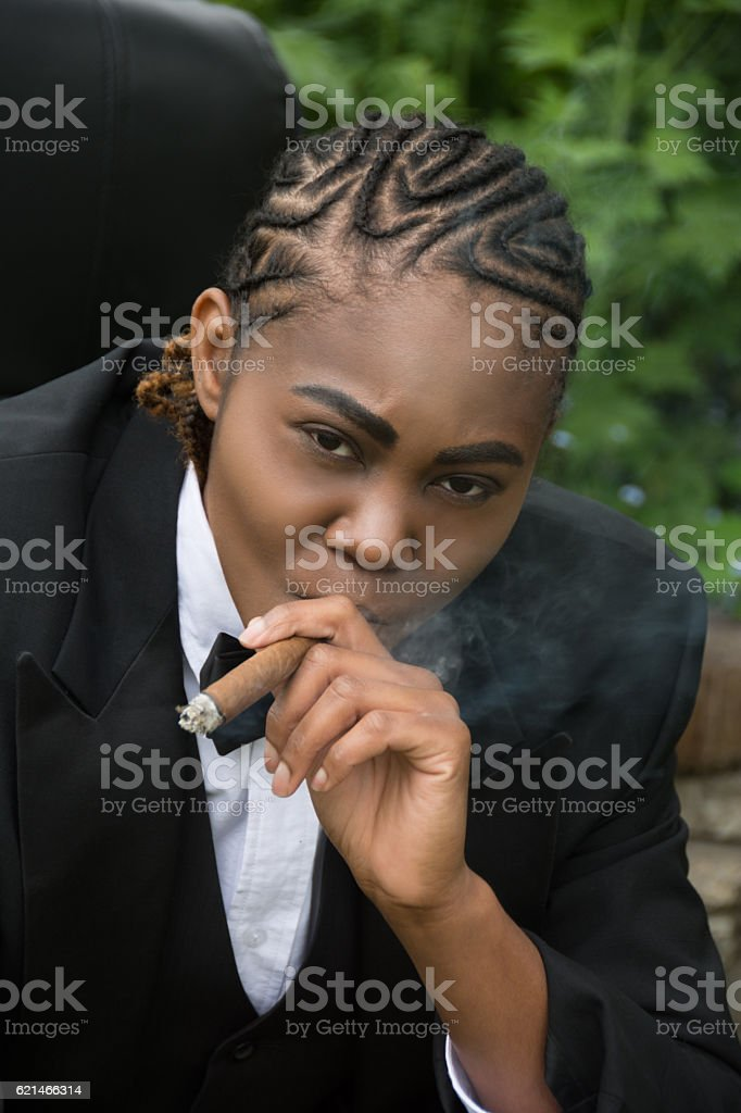 Young black woman in male drag,leaning forward with cigar. stock photo